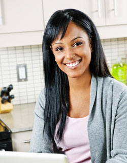 Image of a smiling women in her kitchen in front of her laptop