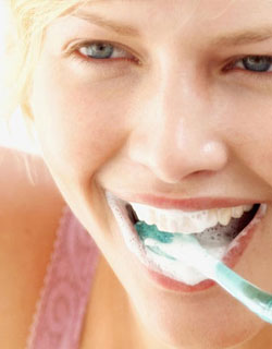 Periodontal Therapy - Image of a woman brushing her teeth