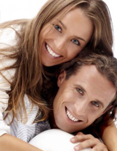 Image of a young couple smiling after receiving smile design therapy from Miami Cosmetic Dentist Dr. Cascante