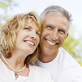 A older couple with beautiful, restored teeth, thanks to restorative dentistry