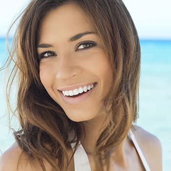 A happy woman smiling because of getting cosmetic dentistry