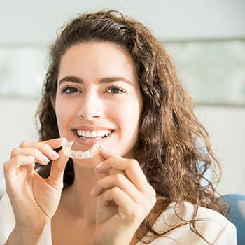 A woman putting on Invisalign aligners for a straight smile