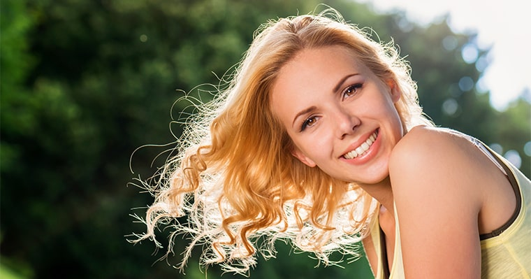 A blonde woman smiling after discovering the cost of Invisalign clear aligners
